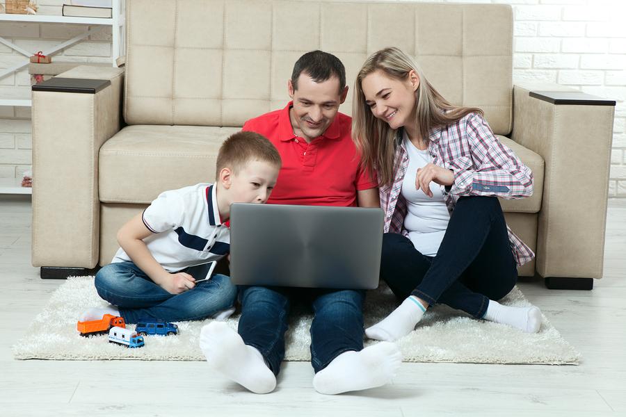 Familie sitzt zuhause am Boden mit Tablet